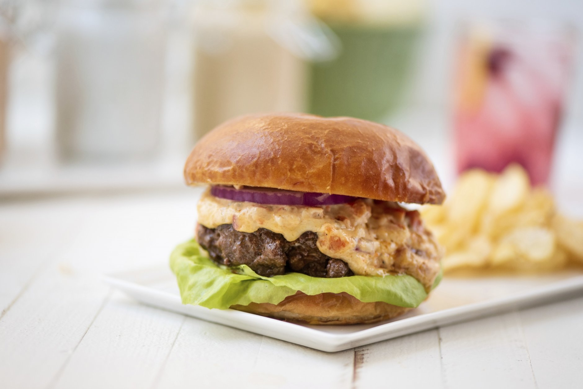 This May 2018 photo shows a burger with pimento cheese in New York. This dish is from a recipe by Katie Workman. (Cheyenne Cohen via AP)