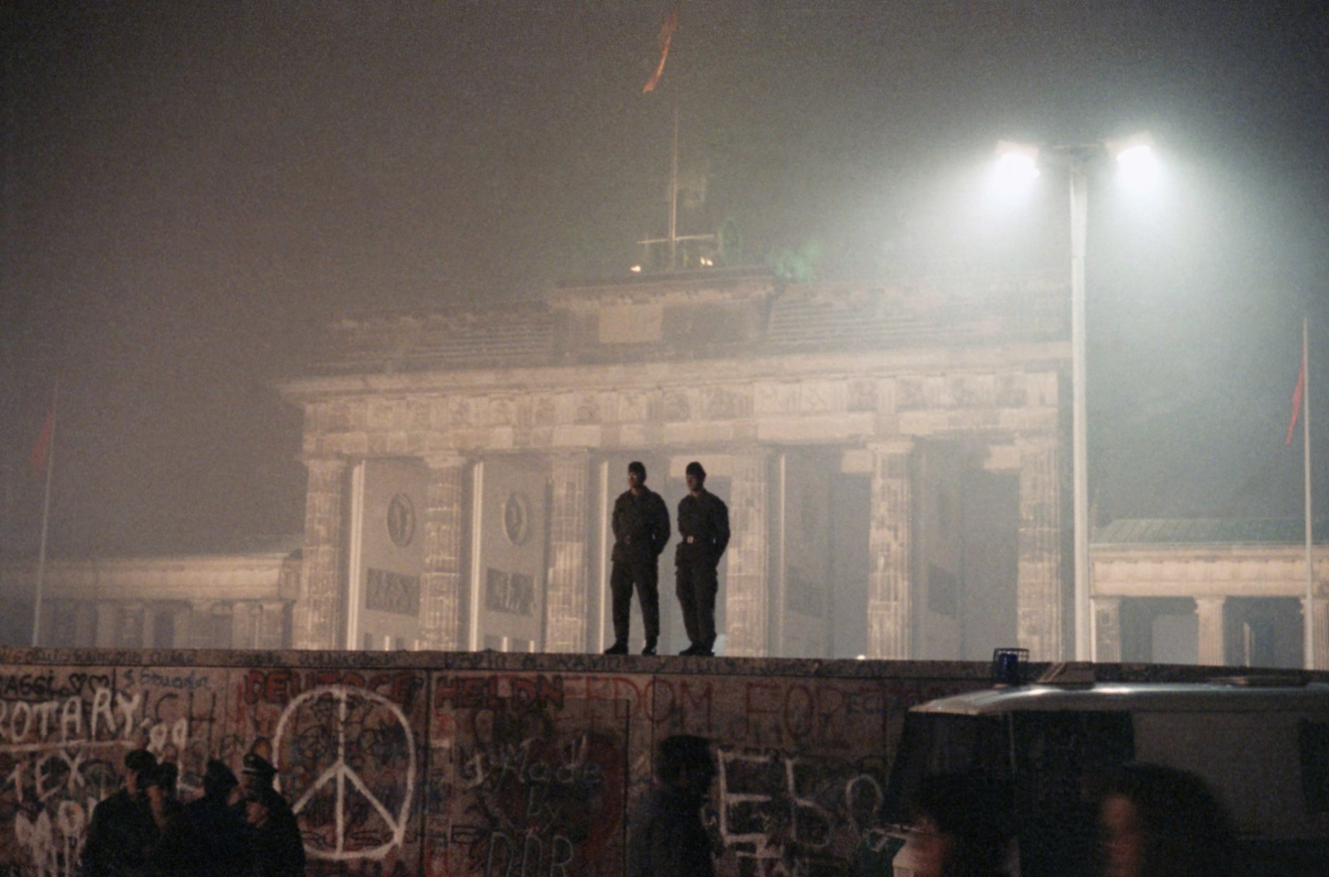 FILE - In this Nov. 14, 1989 file photo two East German border guards patrolled atop of Berlin Wall with the illuminated Brandenburg Gate in background, in Berlin. An artist collective plan to rebuild the Berlin wall during an art project in Berlin in October.  (AP Photo/Jockel Finck, file)