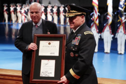 U.S. Army Chief of Staff Gen. Mark A. Milley (R) presents Sen. John McCain (R-AZ) (L) with the Outstanding Civilian Service Medal during a special Twilight Tattoo performance Nov. 14, 2017 at Fort Myer in Arlington, Virginia. Sen. McCain was honored for over 63 years of dedicated service to the nation and the U.S. Navy.  (Photo by Alex Wong/Getty Images)