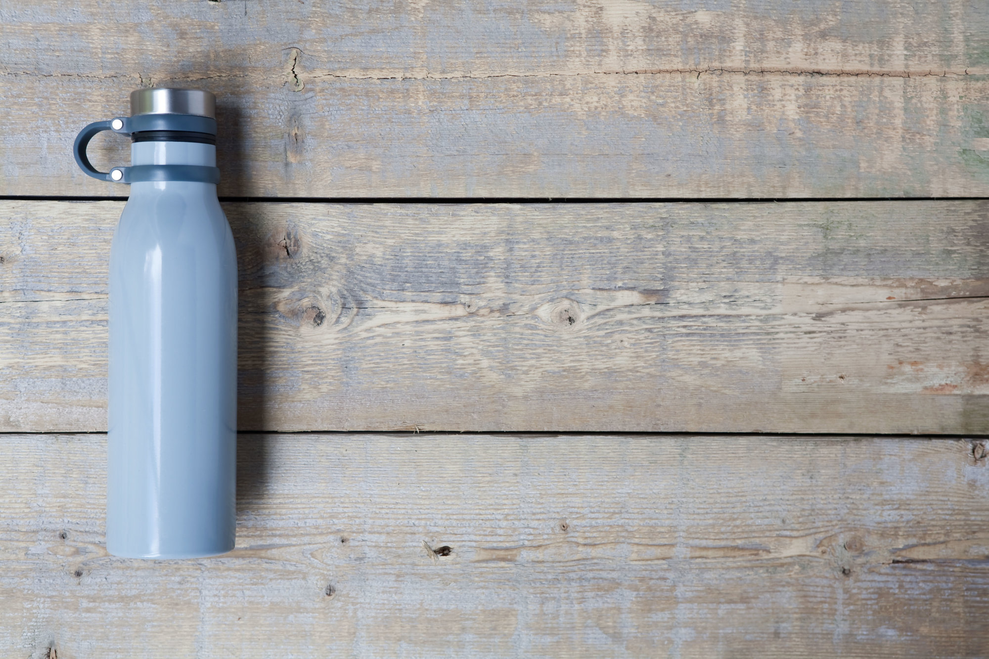 Blue stainless steel, reusable drink container flat lay on a light brown wooden table, with copy space. Horizontal.