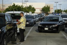 A man fills up his truck as other vehicles line up behind for gasoline at a Costco in preparation for Hurricane Lane, Wednesday, Aug. 22, 2018, in Kapolei, Hawaii. (AP Photo/John Locher)