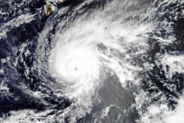 This NASA satellite natural-color image made at at 10:45 a.m. Hawaii Standard Time (20:45 GMT) on Tuesday, Aug. 21, 2018, shows Hurricane Lane as a powerful category 4 storm with maximum sustained winds of 250 kilometers (155 miles) per hour. The Big Island of Hawaii is at upper left. Hurricane Lane has weakened as it approaches Hawaii but was still expected to pack a wallop, forecasters said Wednesday, Aug. 22, as people hurried to buy water and other supplies and the Navy moved its ships to safety.  (NASA via AP)
