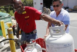 City Mill hardware store sales associate Thom West, left, fills up several propane tanks for Tony Cao, Wednesday, Aug. 22, 2018, in Honolulu. Cao said he waited nearly two hours in line for propane. Although he already stocked up on fresh food, Cao the most important things to have during Hurricane Lane were Spam and Vienna savage as you don't need to cook them. Hurricane Lane has weakened as it approaches Hawaii but was still expected to pack a wallop, forecasters said Wednesday. (AP Photo/Marco Garcia)