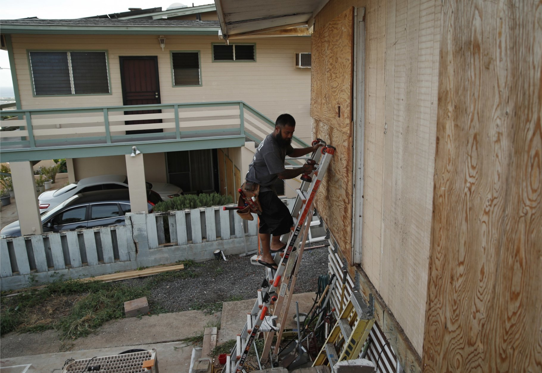 Kaipo Popa secures plywood to protect windows on a home in preparation for Hurricane Lane, Wednesday, Aug. 22, 2018, in Kapolei, Hawaii. As emergency shelters opened, rain began to pour and cellphone alerts went out, the approaching hurricane started to feel real for Hawaii residents.(AP Photo/John Locher)