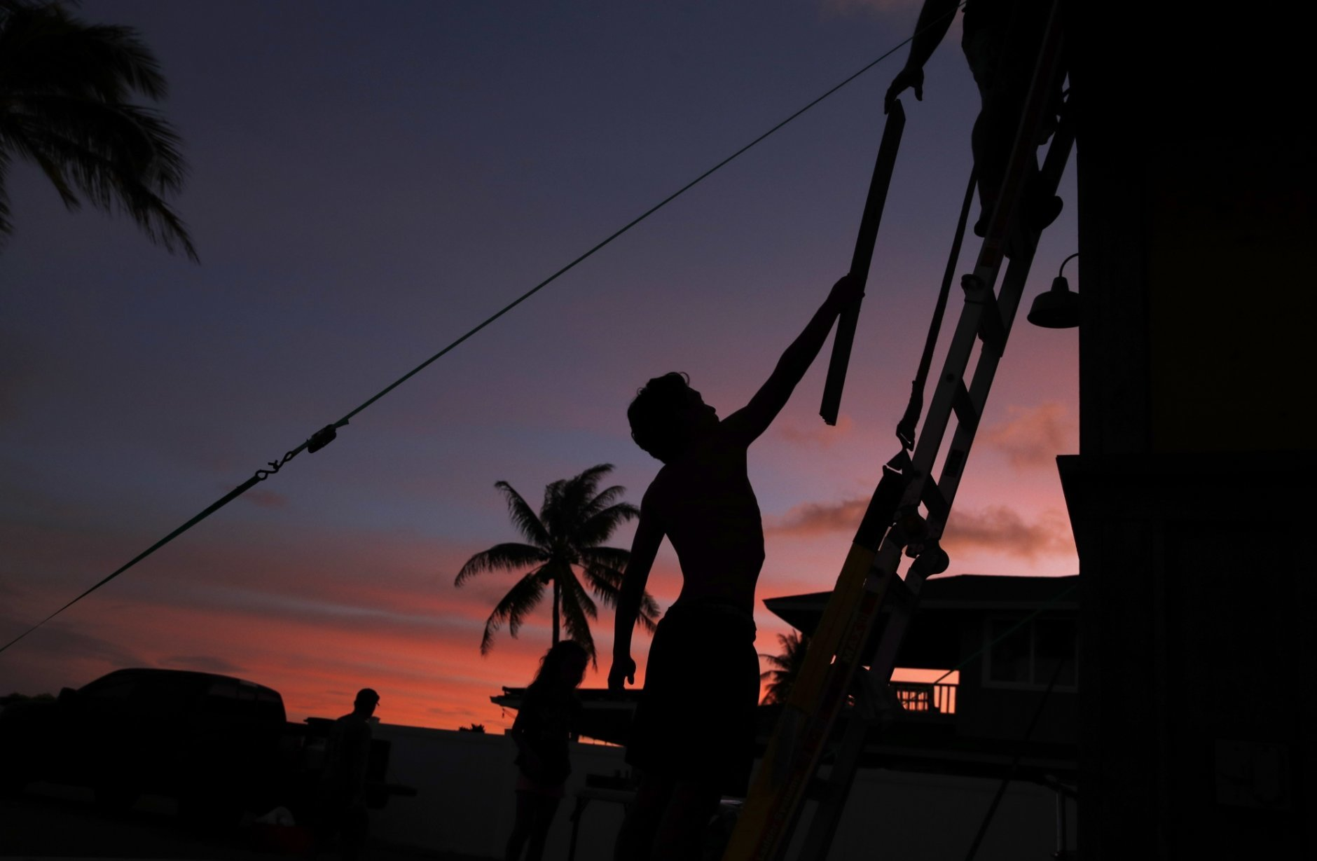 Kainalu Kitashima hands his father a piece of wood to help tie down their tiny home in preparation for Hurricane Lane, Wednesday, Aug. 22, 2018, along Ewa Beach in Honolulu. As emergency shelters opened, rain began to pour and cellphone alerts went out, the approaching hurricane started to feel real for Hawaii residents.(AP Photo/John Locher)