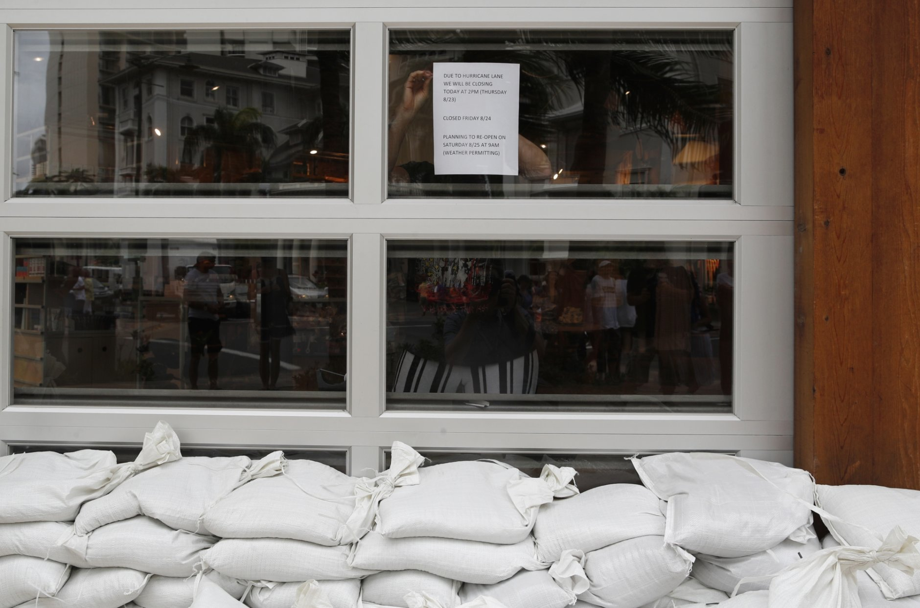 A woman tapes up a sign letting people know a store with stacked sandbags will close soon in preparation for Hurricane Lane, Thursday, Aug. 23, 2018, in Honolulu. (AP Photo/John Locher)