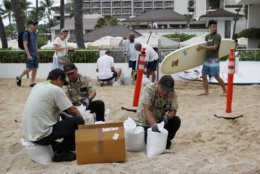 Hotel employees fill sandbags along the beach in preparation for Hurricane Lane, Thursday, Aug. 23, 2018, in Honolulu. Hurricane Lane continues to move northwest and tropical storm conditions were expected to reach the Big Island later Thursday morning with hurricane conditions by nightfall. (AP Photo/John Locher)