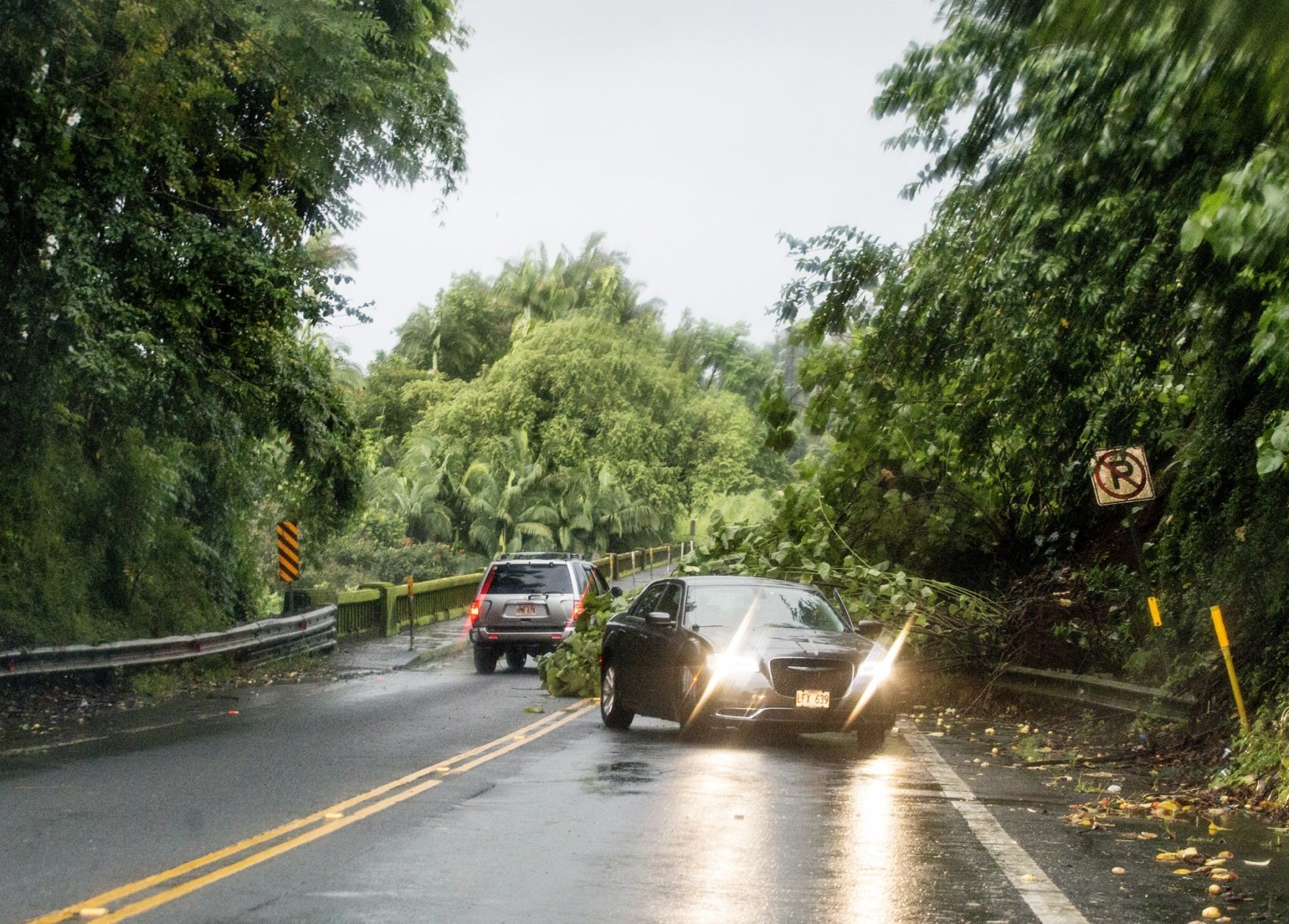A landslide from heavy rains blocks the Hilo bound lane at the Honolii bridge on Highway 19 Thursday, Aug. 23, 2018, in Hilo, Hawaii. Hurricane Lane soaked Hawaii's Big Island on Thursday, dumping nearly 20 inches of rain in nearly 24 hours as residents stocked up on supplies and tried to protect their homes ahead of the state's first hurricane since 1992. (Hollyn Johnson/Hawaii Tribune-Herald via AP)