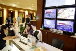 With several monitor displaying hurricane information in several different languages behind them, two women sit at a desk inside a Waikiki hotel, Wednesday, Aug. 22, 2018, in Honolulu. Hurricane Lane has weakened as it approaches Hawaii but was still expected to pack a wallop, forecasters said Wednesday. (AP Photo/Marco Garcia)