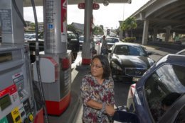 In this photo taken Tuesday, August 21, 2018, lines form at a gas station before the arrival of a hurricane in Honolulu. Hurricane Lane has weakened as it approaches Hawaii but was still expected to pack a wallop, forecasters said Wednesday, as people hurried to buy water and other supplies and the Navy moved its ships to safety. (Craig T. Kojima/Honolulu Star-Advertiser via AP)