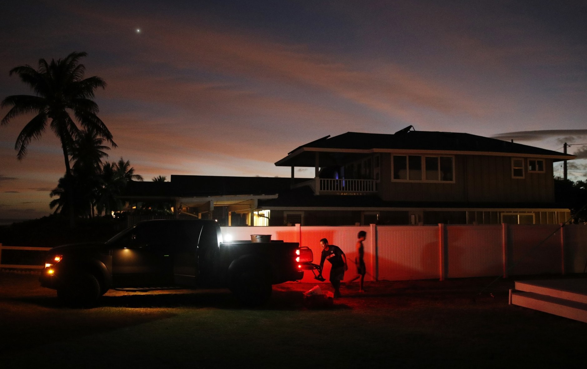 Jay Kitashima, left, loads up his truck after securing his tiny home in preparation for Hurricane Lane, Wednesday, Aug. 22, 2018, along Ewa Beach in Honolulu. As emergency shelters opened, rain began to pour and cellphone alerts went out, the approaching hurricane started to feel real for Hawaii residents. (AP Photo/John Locher)