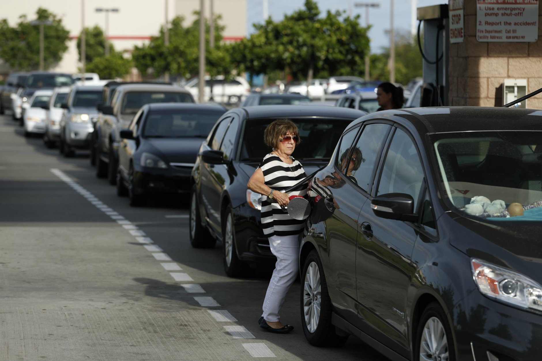 A woman fills up her car as other vehicles line up behind her for gasoline at a Costco in preparation for Hurricane Lane, Wednesday, Aug. 22, 2018, in Kapolei, Hawaii. (AP Photo/John Locher)
