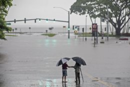 People stand near flood waters from Hurricane Lane making the intersection of Kamehameha Avenue and Pauahi Street impassable Thursday, Aug. 23, 2018, in Hilo, Hawaii. Hurricane Lane soaked Hawaii's Big Island on Thursday, dumping nearly 20 inches of rain in nearly 24 hours as residents stocked up on supplies and tried to protect their homes ahead of the state's first hurricane since 1992. (Hollyn Johnson/Hawaii Tribune-Herald via AP)