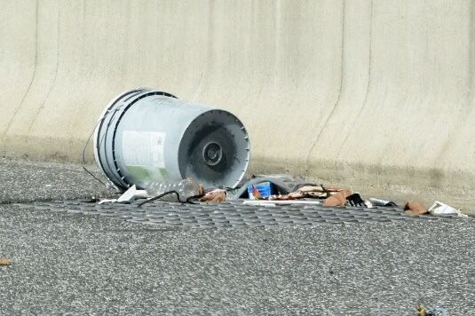Construction materials are a common form of highway debris. A bucket rolls along the edge of Interstate 295 near the Maryland state line. (WTOP/Dave Dildine)