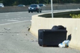 A couch rests on the shoulder of Interstate 295 in the District. Furniture tied with metal objects for the third most common form of debris on D.C. area highways. (WTOP/Dave Dildine)