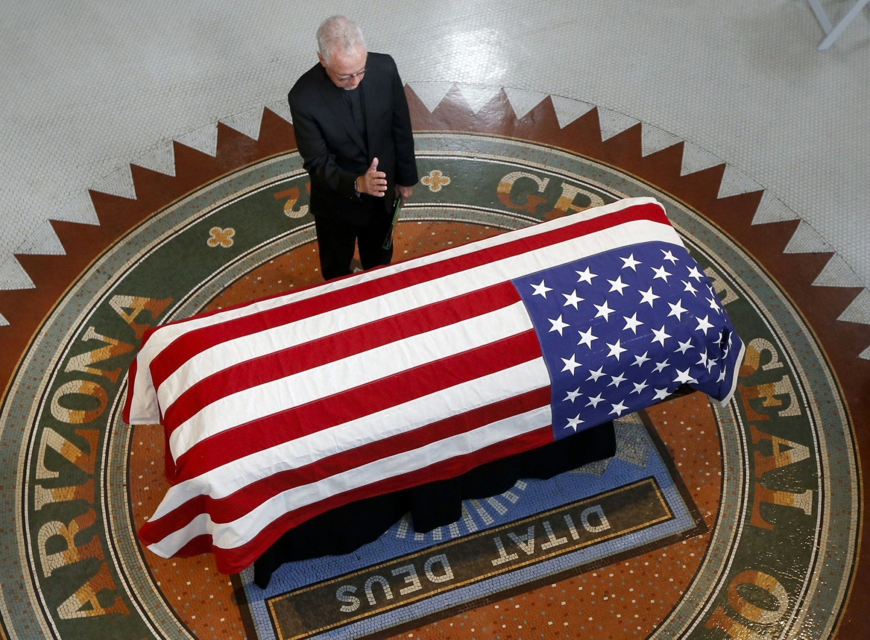 Father Edward A. Reese prays over the casket during a memorial service for Sen. John McCain, R-Ariz. at the Arizona Capitol on Wednesday, Aug. 29, 2018, in Phoenix. (AP Photo/Ross D. Franklin, Pool)