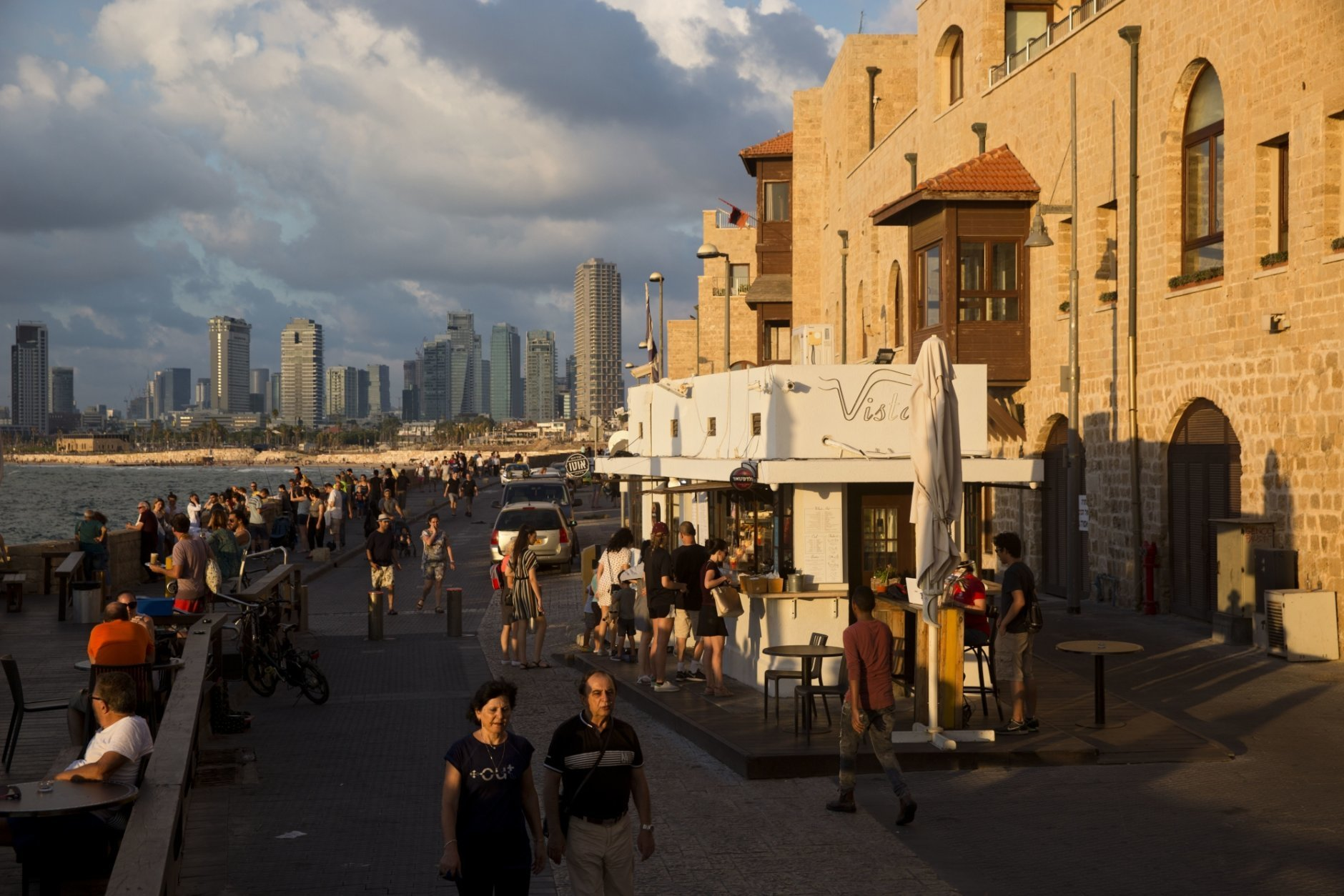 In this Saturday, July 28, 2018 photo, people enjoy the day on Jaffa's promenade overlooking Tel Aviv's skyline and the Mediterranean sea in Jaffa, Israel. Israel's port city of Jaffa is an ancient place. Today glass towers and modern apartment complexes rise amid Jaffa's old white stone buildings. It's famous for its flea market and hummus cafes. But visitors will also find trendy bars, galleries and boutiques. (AP Photo/Oded Balilty)