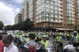 Outside the Foggy Bottom Metro station, a large group of media, counterprotesters and police greet Unite The Right 2 rally participants. (WTOP/ Max Smith)