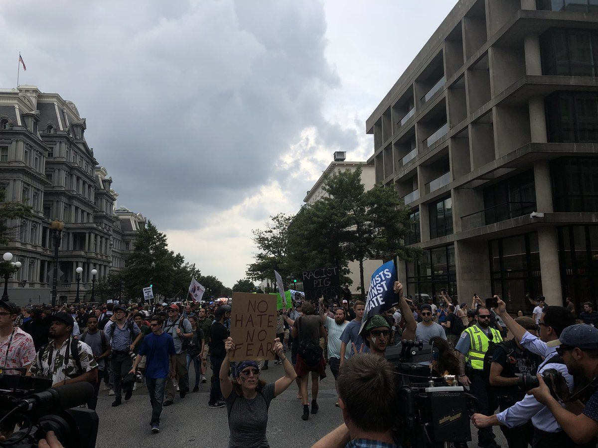 Counterprotesters walk in front of the group of Unite The Right protesters. They are mostly surrounded by D.C. Police. (WTOP/Max Smith)