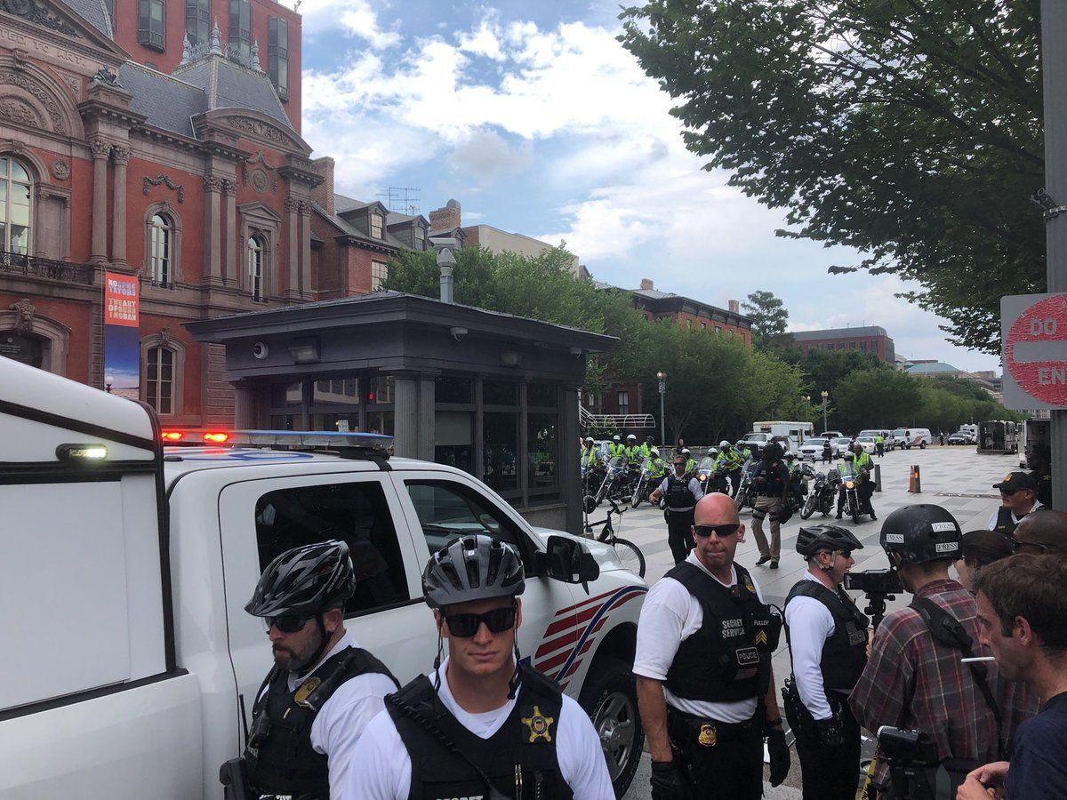 Counterprotesters walk in front of the group of Unite The Right protesters. The protesters are mostly surrounded by D.C. Police. (WTOP/Max Smith)