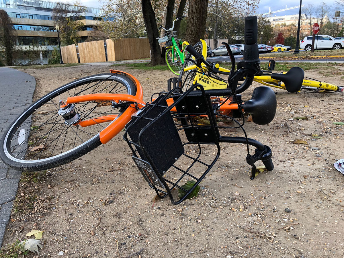 A Spin bike is seen in the foreground; an Ofo bike is lying down behind it. Five companies remain in D.C.: Lime, Jump, Spin, Bird and Skip, although Bird and Skip offer scooters, not dockless bikes. Lime offers bikes, ebikes and scooters. (WTOP/Kate Ryan)