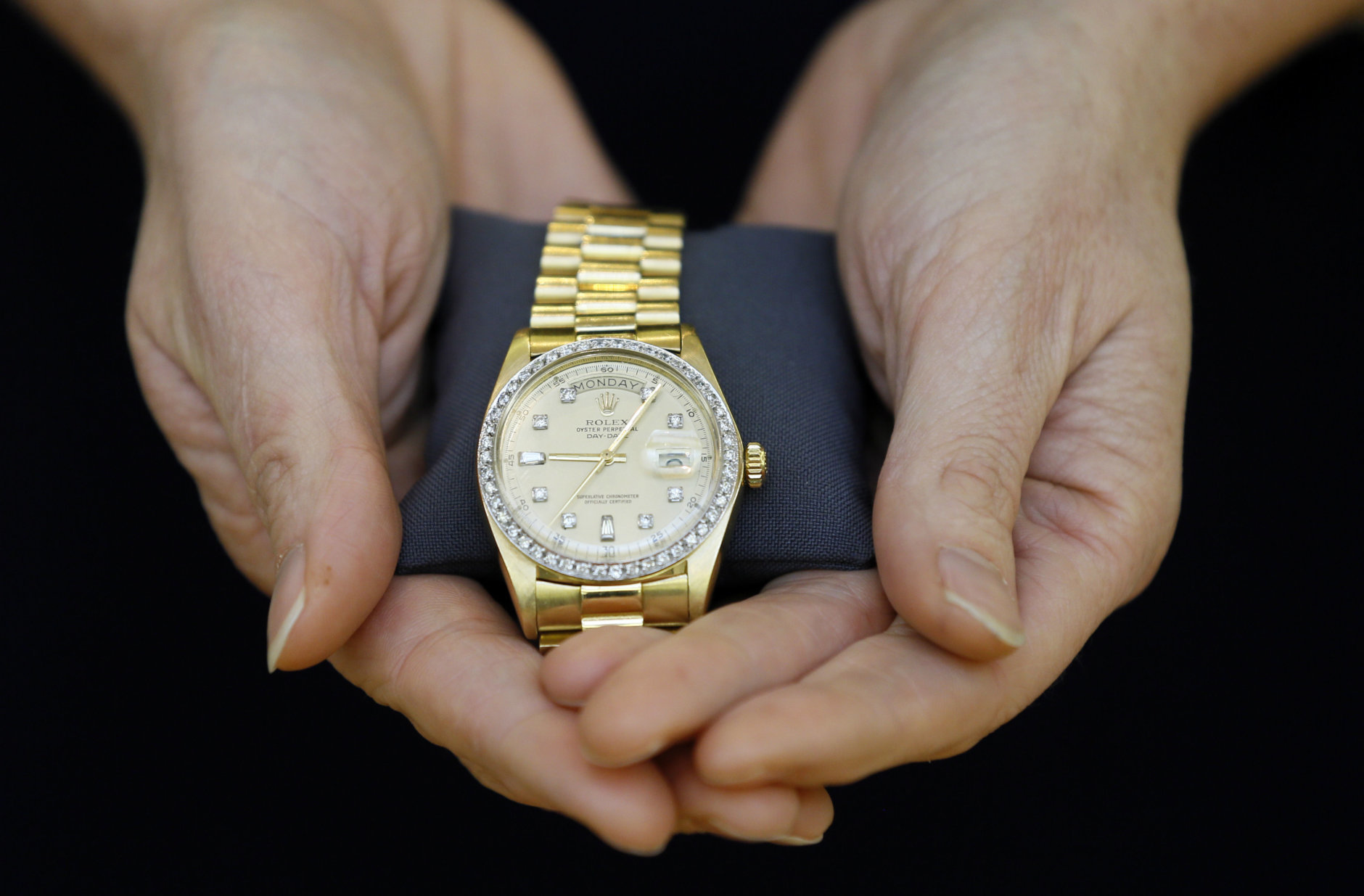 A Christie's specialist displays a Rolex watch given to Elvis Presley by his manager for Christmas in 1976, during a photocall at the auction rooms in London, Friday, Nov. 23, 2012. The watch estimated at 6,000- 8,000 pounds (9,500- 12,750 US Dollars) will go on sale in the Pop Culture auction on Nov. 29 in London. (AP Photo/Kirsty Wigglesworth)