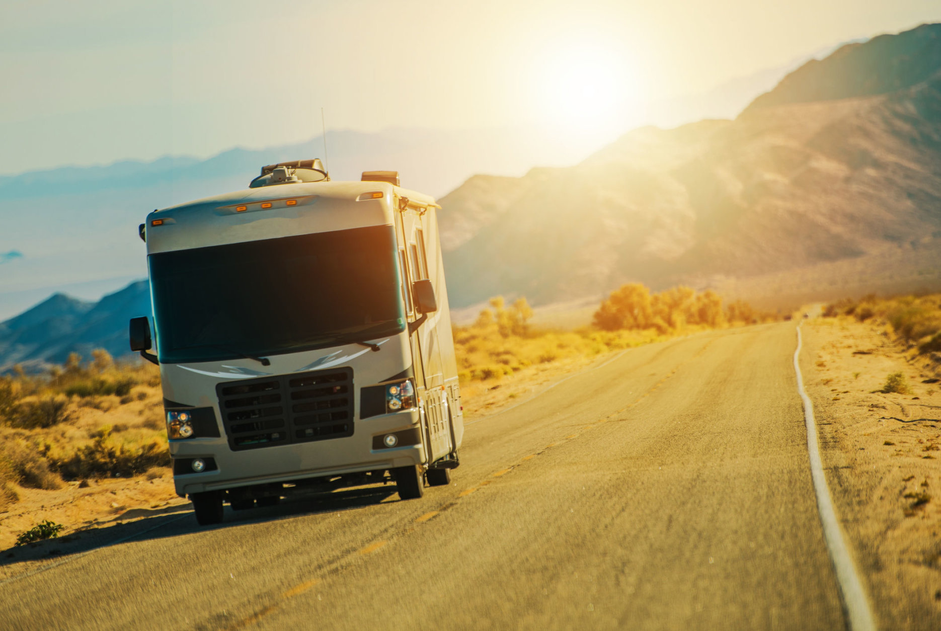 Motorhome on the Desert Road Somewhere in the Southern California Mojave Desert. Class A Gasoline Engine Motorcoach. United States of America. American RVing.