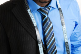 This is an image of business man wearing a tape measure across his suit and shirt.