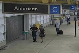The suspects, a man and a woman, arrive at the airport in the ticketing/departures area, walking south toward Door 6. (Courtesy Metropolitan Washington Airports Authority)