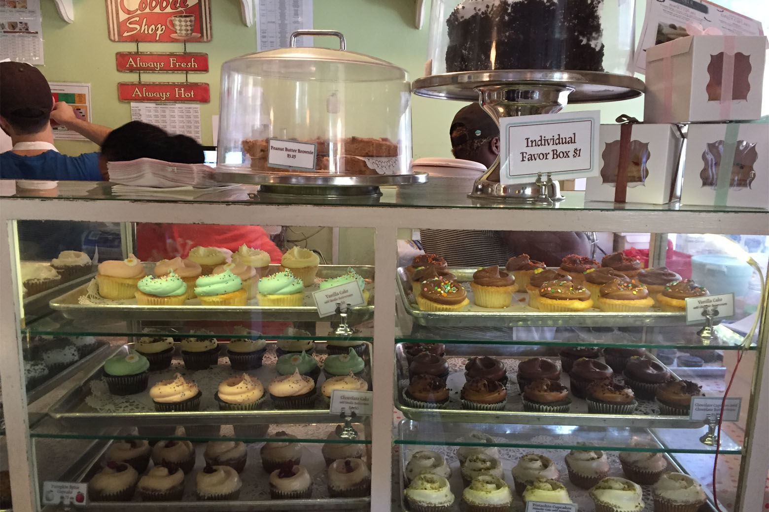 """This Oct. 20, 2017 photo shows display cases laden with luscious cupcakes at Magnolia Bakery in Greenwich Village in New York. The bakery was made famous by a """"Sex & the City"""" episode. (AP Photo/Beth J. Harpaz)"""