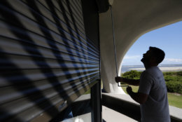 Chris Brace, from Charleston, S.C. lowers hurricane shutters on a client's house in preparation for Hurricane Florence at Sullivan's Island, S.C., Monday, Sept. 10, 2018. Brace said that after S.C. Gov. Henry McMaster ordered an evacuation the property owner asked for the house to be boarded up. (AP Photo/Mic Smith)