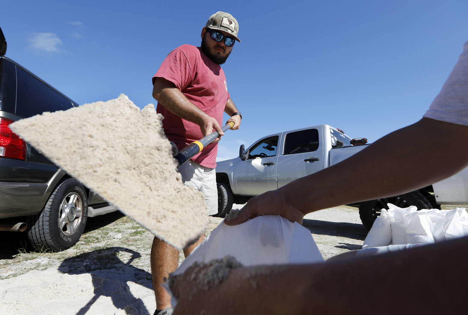 Walker Townsend, at left, from the Isle of Palms, S.C., fills a sand bag while Dalton Trout, at right, holds the bag at the Isle of Palms municipal lot where the city was giving away free sand in preparation for Hurricane Florence at the Isle of Palms S.C., Monday, Sept. 10, 2018. (AP Photo/Mic Smith)