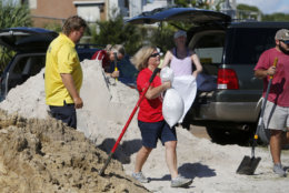 Residents of the Isle of Palms, S.C., fill sand bags at the Isle of Palms municipal lot where the city was giving away free sand in preparation for Hurricane Florence at the Isle of Palms S.C., Monday, Sept. 10, 2018. (AP Photo/Mic Smith)