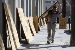 CORRECTS DATE  - Preston Guiher carries a sheet of plywood as he prepares to board up a Wells Fargo bank in preparation for Hurricane Florence in downtown Charleston, S.C., Tuesday, Sept. 11, 2018. (AP Photo/Mic Smith)