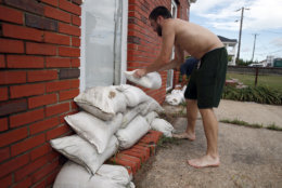 Adam Bazemore places sandbags in the doorways, Tuesday, Sept. 11, 2018, in the Willoughby Spit area of Norfolk, Va., as he makes preparations for Hurricane Florence. (AP Photo/Alex Brandon)
