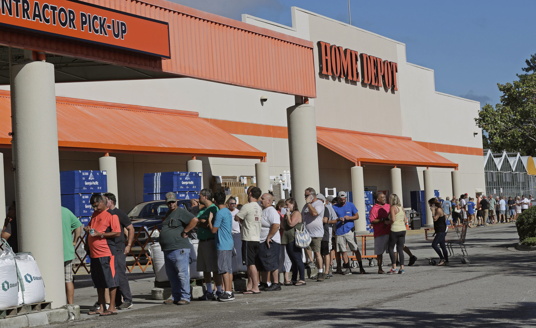 People line up outside a Home Depot for a new supply of generators and plywood in advance of Hurricane Florence in Wilmington, N.C., Wednesday, Sept. 12, 2018. Florence exploded into a potentially catastrophic hurricane Monday as it closed in on North and South Carolina, carrying winds up to 140 mph (220 kph) and water that could wreak havoc over a wide stretch of the eastern United States later this week. (AP Photo/Chuck Burton)