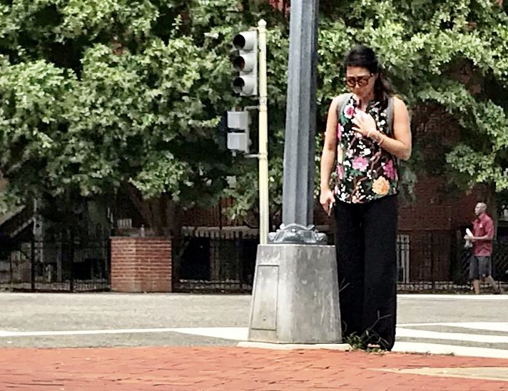 A woman cries on the street near where Wendy Martinez was stabbed. (WTOP/Neal Augenstein)