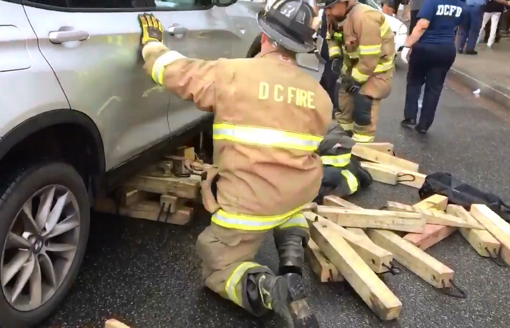 Videos tweeted by the D.C. Fire and EMS Service showed firefighters working to free the man who had become trapped under a silver SUV. (Courtesy D.C. Fire and EMS)