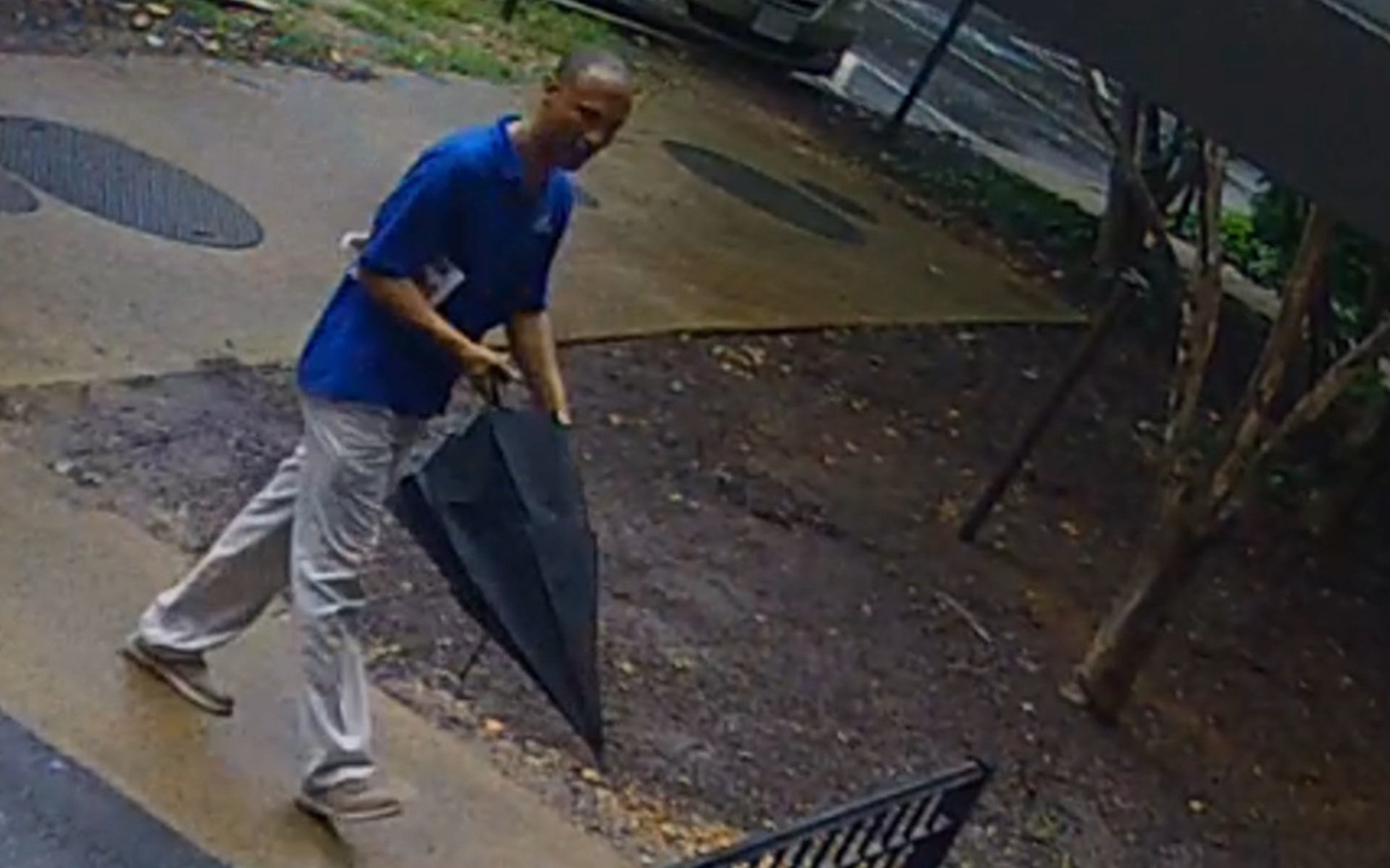 The suspect captured on surveillance video is described as black man, about 60 years, between 5 feet, 10 inches and 6 feet tall with a medium build. He has dark short curly hair with some gray. He was wearing a bright blue shirt, khaki pants, tan shoes and was carrying an umbrella at the time, police said. (Courtesy Arlington County police)