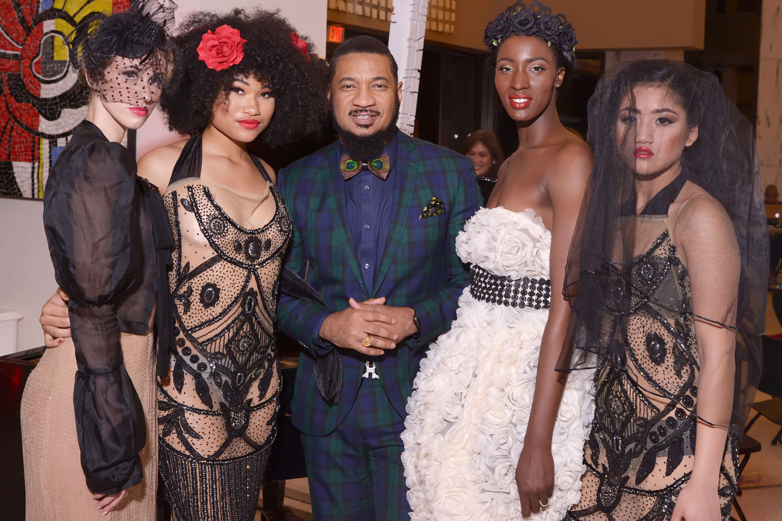 Models wearing dresses by Washington, DC-based designer Ean Williams pose with the designer following the runway show at DC Fashion Week's 2018 International Couture Collections at the Embassy of France