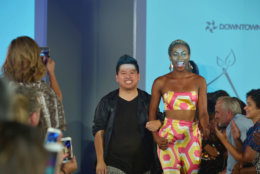 "Fashion designer Frank Huynh of Fashions by Le Tam takes a final bow with a model wearing pieces from the label's spring/summer 2019 line at the DowntownDC Business Improvement District (BID) District of Fashion runway show. (Courtesy Shannon Finney/<a href=""https://www.shannonfinneyphotography.com/index"" target=""_blank"" rel=""noopener noreferrer"">shannonfinneyphotography.com</a>)"