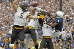 Appalachian State defenders Thomas Hennigan (5), Corey Sutton (2) and Josh Thomas (7), break up a pass intended for Penn State's KJ Hamler (1) in the end zone during the first half of an NCAA college football game in State College, Pa., Saturday, Sept. 1, 2018. (AP Photo/Chris Knight)