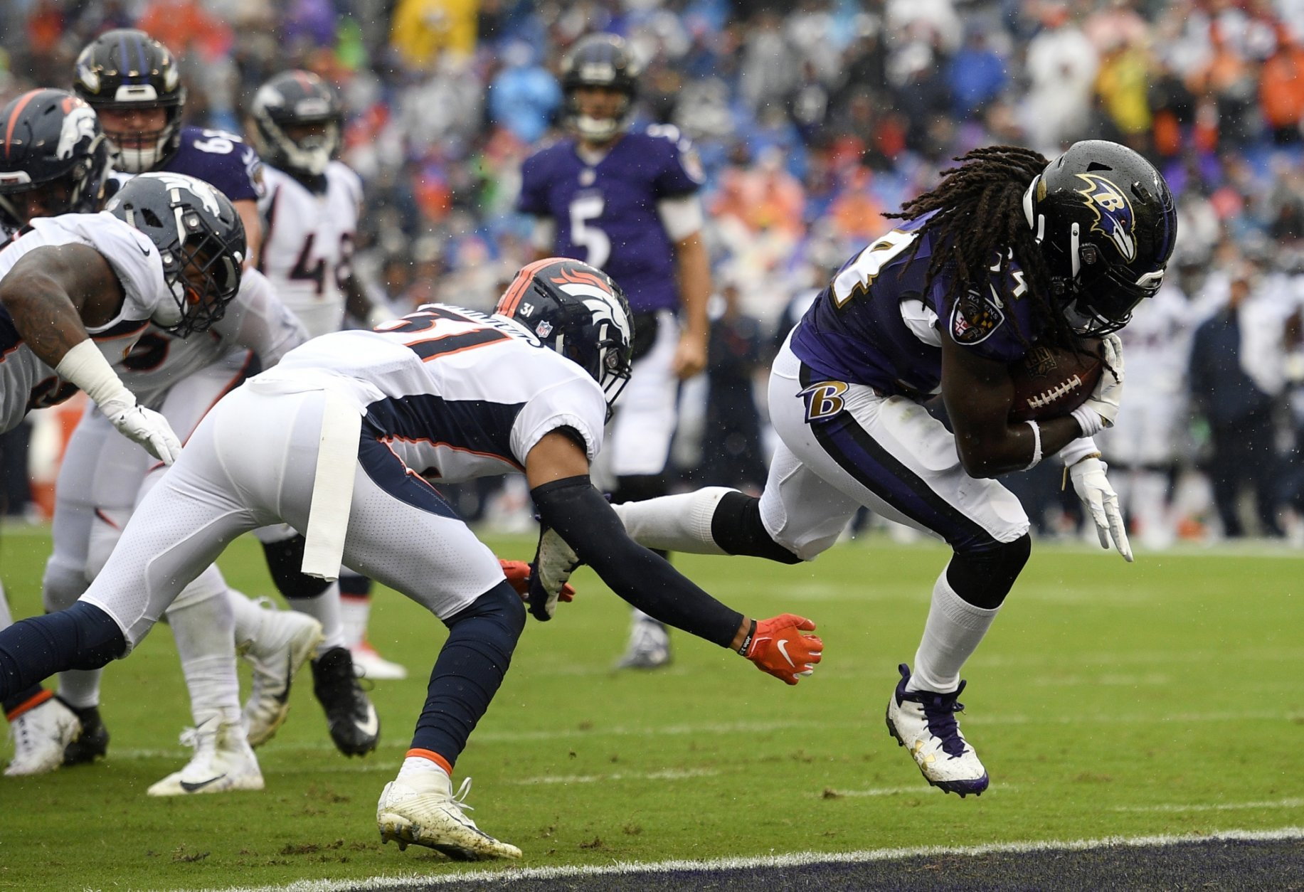 Baltimore Ravens running back Alex Collins, right, rushes past Denver Broncos defensive back Justin Simmons for a touchdown in the first half of an NFL football game, Sunday, Sept. 23, 2018, in Baltimore. (AP Photo/Nick Wass)