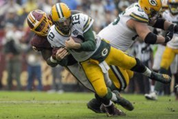 Green Bay Packers quarterback Aaron Rodgers (12) is sacked by Washington Redskins defensive tackle Da'Ron Payne during the second half of an NFL football game, Sunday, Sept. 23, 2018 in Landover, Md. (AP Photo/Mark Tenally)