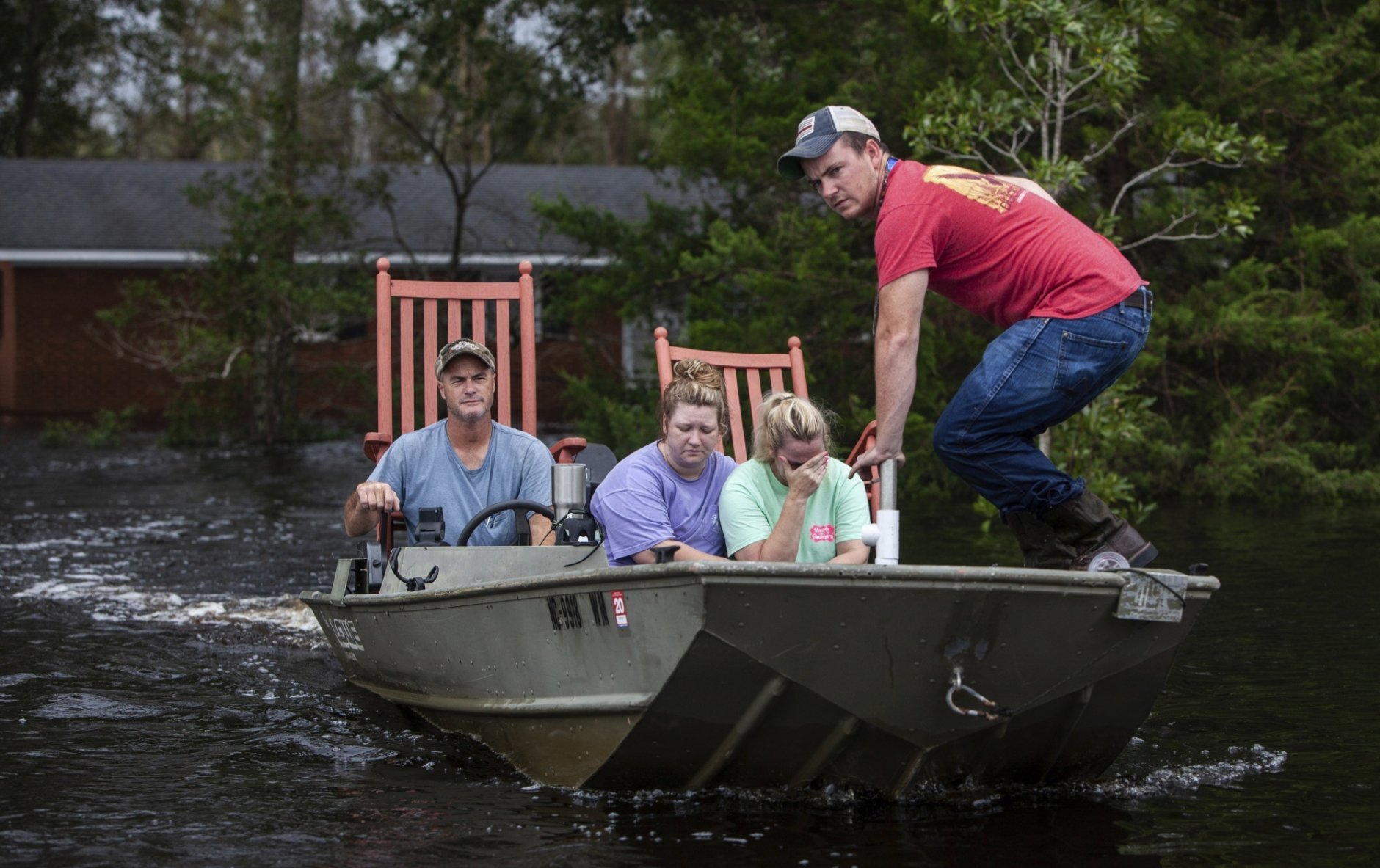 From left, Mike Haddock, 48, Katlyn Humphrey, 19, Michelle Haddock, 45, and Justin Humphrey, 24, remove possessions from the Haddock's flooded home using a jon boat Monday, Sept. 17, 2018 in Trenton, N.C. following Hurricane Florence. (Travis Long/The News & Observer via AP)