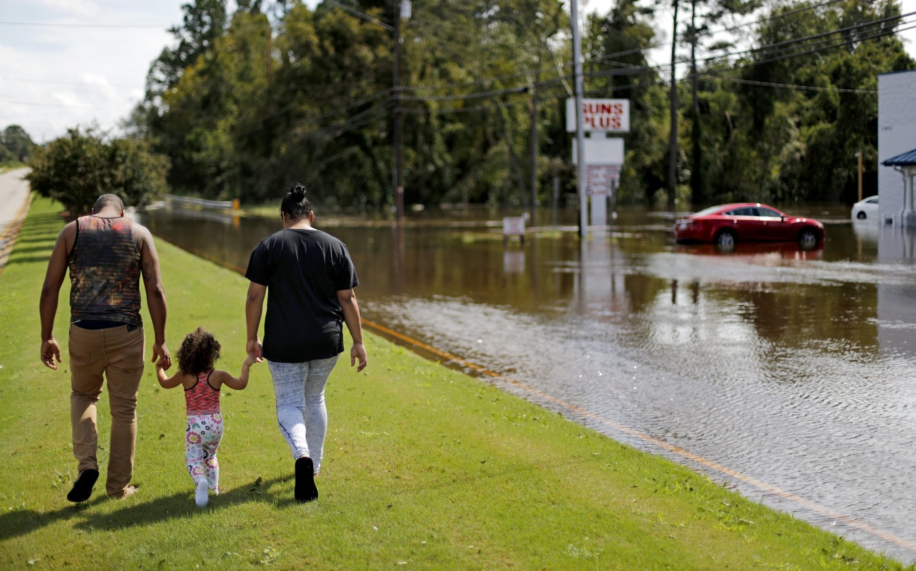 A couple walks with their daughter after checking on their flooded home in the aftermath of Hurricane Florence in Spring Lake, N.C., Monday, Sept. 17, 2018. (AP Photo/David Goldman)