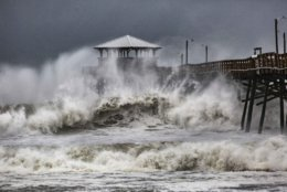 Waves slam the Oceana Pier & Pier House Restaurant in Atlantic Beach, N.C.,  Thursday, Sept. 13, 2018 as Hurricane Florence approaches the area. (Travis Long/The News & Observer via AP)