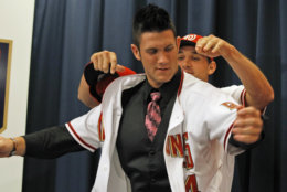 Ryan Zimmerman, right, helps Bryce Harper put on his new jersery, at a news conference where the Washington Nationals introduced Harper as their first overall selection in the 2010 First-Year Player Draft, at Nationals Park in Washington Thursday, Aug. 26, 2010.(AP Photo/Alex Brandon)