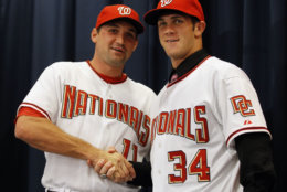 Washington Nationals' Ryan Zimmerman, left, shakes hands with Bryce Harper at a news conference where the Nationals introduced Harper as their first overall selection in the 2010 First-Year Player Draft, at Nationals Park in Washington Thursday, Aug. 26, 2010. Harper  agreed to a $9.9 million, five-year deal with the baseball club last week. (AP Photo/Alex Brandon)
