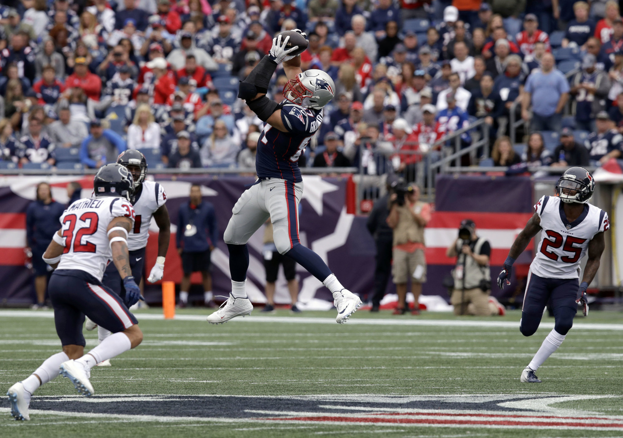 New England Patriots tight end Rob Gronkowski (87) catches a pass between Houston Texans defensive backs Tyrann Mathieu (32) and Kareem Jackson (25) during the second half of an NFL football game, Sunday, Sept. 9, 2018, in Foxborough, Mass. Gronkowski fumbled and Mathieu recovered on the play. (AP Photo/Charles Krupa)